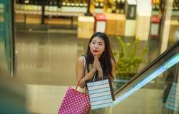 Młoda szczęśliwa i piękna Azjatycka Koreańska kobieta przy centrum handlowe eskalatoru przewożenia torba na zakupy w centrum hand obrazy stock