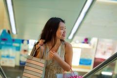 Młoda szczęśliwa i piękna Azjatycka Koreańska kobieta przy centrum handlowe eskalatoru przewożenia torba na zakupy w centrum hand obraz royalty free