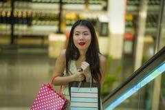 Młoda szczęśliwa i piękna Azjatycka Koreańska kobieta przy centrum handlowe eskalatoru przewożenia torba na zakupy w centrum hand obrazy royalty free