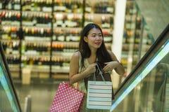 Młoda szczęśliwa i piękna Azjatycka Koreańska kobieta przy centrum handlowe eskalatoru przewożenia torba na zakupy w centrum hand obraz stock