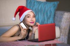 Młoda szczęśliwa i piękna kobieta relaksował w domu leżankę w Santa kapeluszowym używa laptopie płaci dla Bożenarodzeniowej teraź zdjęcia stock