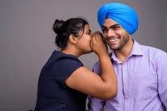 Młoda szczęśliwa Indiańska kobieta szepcze jej uśmiechnięty chłopak obrazy royalty free