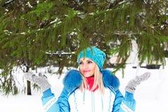 Młoda szczęśliwa kobieta cieszy się śnieg w zimy miasta parku plenerowym Zdjęcie Stock