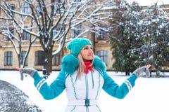 Młoda szczęśliwa kobieta cieszy się śnieg w zimy miasta parku plenerowym Obraz Royalty Free