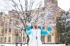 Młoda szczęśliwa kobieta cieszy się śnieg w zimy miasta parku plenerowym Obrazy Royalty Free