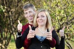 Młoda szczęśliwa kobieta i mężczyzna za jej aprobatami w parku obraz stock