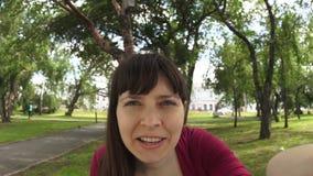 Młoda szczęśliwa kobieta macha jej rękę podczas gdy robić selfie na ławce w parku zbiory wideo
