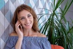 Młoda szczęśliwa kobieta opowiada na telefonie komórkowym z przyjacielem podczas gdy siedzący samotnie w nowożytnym sklep z kawą  zdjęcia royalty free