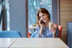 Młoda szczęśliwa kobieta opowiada na telefonie komórkowym z przyjacielem podczas gdy siedzący samotnie w nowożytnym sklep z kawą  zdjęcie stock