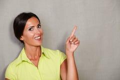 Młoda szczęśliwa kobieta podczas gdy wskazywać oddolny obraz stock