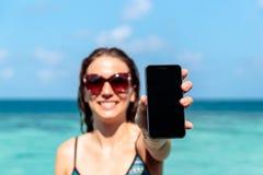 Młoda szczęśliwa kobieta pokazuje pionowo telefonu ekran Jasna b??kitne wody jako t?o zdjęcia royalty free