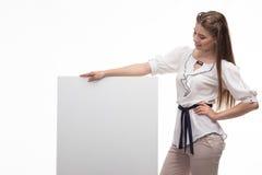 Młoda szczęśliwa kobieta pokazuje prezentację, wskazuje na plakacie fotografia stock