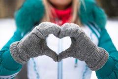 Młoda szczęśliwa kobieta robi sercu plenerowy z rękami w zimy miasta parku Fotografia Stock
