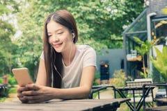 Młoda szczęśliwa kobieta siedzi przy plenerowym parkiem l w przypadkowych ubraniach Zdjęcie Royalty Free