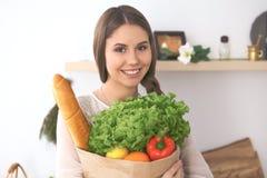 Młoda szczęśliwa kobieta trzyma papierową torbę warzywa i owoc pełno podczas gdy ono uśmiecha się Dziewczyna zrobił zakupy i przy Fotografia Stock