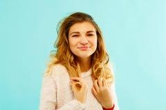 Młoda szczęśliwa kobieta w ciepłym pulowerze nad błękitnym tłem Zdjęcie Royalty Free