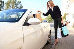 Młoda szczęśliwa kobieta z torba na zakupy blisko samochodu outdoors fotografia royalty free