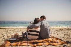 Młoda szczęśliwa kochająca rodzina z małym dzieckiem, cieszący się czas i przytulenie przy plażowym obsiadaniem blisko oceanu, sz Obrazy Royalty Free