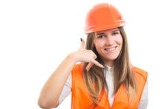 Młoda szczęśliwa konstruktor kobieta gestykuluje wezwanie ja obrazy royalty free