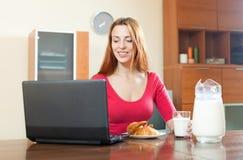 Młoda szczęśliwa miedzianowłosa dziewczyna w różowym używa laptopie podczas breakfas fotografia stock