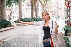 Młoda szczęśliwa modniś dziewczyna z torba na zakupy łapie taxi na zdjęcie stock