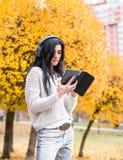 Młoda szczęśliwa nastoletnia dziewczyna używa jej słuchanie i pastylkę muzyka w jesieni miasta parku Spadku stylu obrazek Zdjęcia Stock