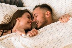 Młoda szczęśliwa para kłama wpólnie w łóżku fotografia royalty free