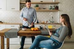 Młoda szczęśliwa para małżeńska w kuchni Mężczyzna stoi kuchennym stołem i przygotowywający śniadaniowego kobieta w ciąży siedzi obrazy stock