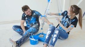 Młoda szczęśliwa para ma zabawę i maluje ich mieszkanie podczas gdy odświeżanie zdjęcie wideo