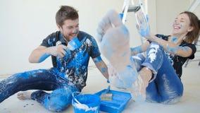 Młoda szczęśliwa para ma zabawę i maluje ich mieszkanie podczas gdy odświeżanie zbiory wideo