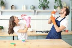 Młoda szczęśliwa para ma zabawę podczas gdy robić czyścić w domu i śpiewać zdjęcia royalty free