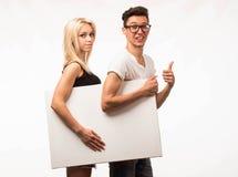 Młoda szczęśliwa para pokazuje prezentację wskazuje plakat zdjęcia royalty free