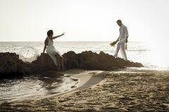 Młoda szczęśliwa para relaksuje wpólnie na plaży kołysa przy wschodem słońca Obrazy Stock