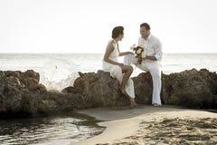 Młoda szczęśliwa para relaksuje wpólnie na plaży kołysa przy wschodem słońca Zdjęcie Royalty Free