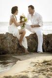 Młoda szczęśliwa para relaksuje wpólnie na plaży kołysa przy wschodem słońca Fotografia Royalty Free