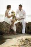 Młoda szczęśliwa para relaksuje wpólnie na plaży kołysa przy wschodem słońca Obraz Stock