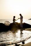 Młoda szczęśliwa para relaksuje wpólnie na plaży kołysa przy wschodem słońca Obrazy Royalty Free