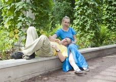 Młoda szczęśliwa para siedzi w arbour splatać zieleniach Obrazy Royalty Free