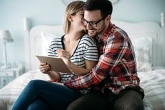 Młoda szczęśliwa para używa pastylkę w sypialni Zdjęcia Royalty Free