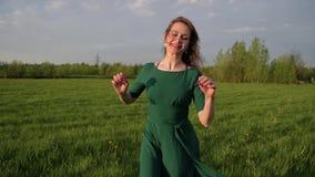 Młoda szczęśliwa piękna kobieta w sukni biega wzdłuż zielonego pola zbiory
