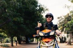 Młoda szczęśliwa, przystojna męska motocyklista jazda na motocyklu daje i obraz royalty free