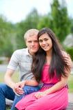 Młoda szczęśliwa różnorodna para siedzi wpólnie outdoors Obrazy Royalty Free