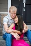 Młoda szczęśliwa różnorodna para siedzi wpólnie outdoors Zdjęcia Stock