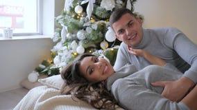Młoda szczęśliwa rodzina wpólnie kłama na łóżku i spojrzeniach przy kamerą na tle xmas drzewo zdjęcie wideo
