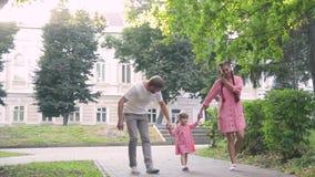 Młoda szczęśliwa rodzina z małym pięknym dzieckiem chodzi w lato parku przy zmierzchem z niebieskimi oczami zdjęcie wideo