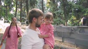 Młoda szczęśliwa rodzina z małym pięknym dzieckiem chodzi w lato parku przy zmierzchem z niebieskimi oczami zbiory