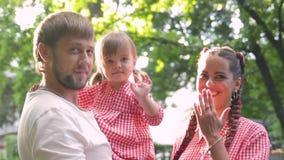 Młoda szczęśliwa rodzina z małym pięknym dzieckiem chodzi w lato parku przy zmierzchem z niebieskimi oczami zbiory wideo