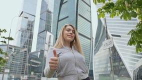 Młoda szczęśliwa rozochocona blondynki dziewczyna pokazuje kciuk up przeciw tłu wieżowowie i drapacze chmur zbiory wideo