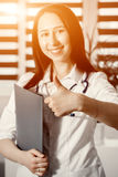 Młoda szczęśliwa rozochocona lekarka w bielu seansu jednolitym OK lub zatwierdzenie znak z kciukiem up Obraz Stock