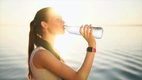 Młoda szczęśliwa uśmiechnięta kobieta pije wodę od butelki blisko morza zbiory